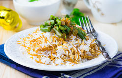 Rice plov with vermicelli, green beans and onions Stock Photo