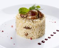 Rice with porcini mushrooms. On a white plate stock photography