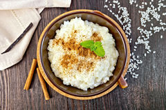 Rice porridge with cinnamon in bowl on board top Royalty Free Stock Image