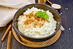 Rice porridge with cinnamon in bowl on dark board Royalty Free Stock Images