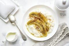 Rice porridge with coconut milk,caramelized banana and cinnamon. Stock Photo