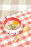 Rice porridge with egg in cute bowl. On chess pattern royalty free stock image