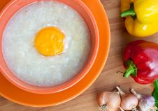 Rice porridge with egg in orange bowl. Stock Image