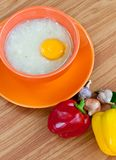 Rice porridge with egg in orange bowl. Royalty Free Stock Photography
