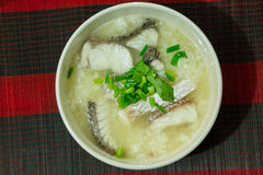 Rice porridge with fish. On red and black background Stock Photography