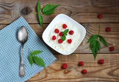 Rice porridge with fresh raspberries on a wooden Board Royalty Free Stock Images