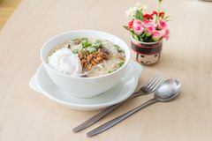 Rice porridge with garlic and egg breakfast in white bowl on wooden table stock images