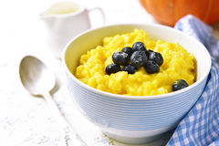Rice porridge with pumpkin and fresh blueberry. Stock Images