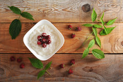 Rice porridge with raspberries on rustic wooden background Stock Image