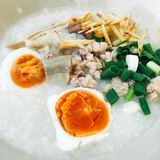 Rice porridge with salted egg. Topping with onions ginger and vegetable is one type of breakfast Stock Images