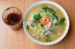 Rice porridge with seafood and fried chili pasted in glass. Rice porridge with seafood and fried chili pasted in the glass Stock Image