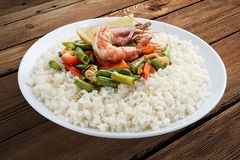Rice porridge with shrimps and vegetables. On a wooden background royalty free stock photos