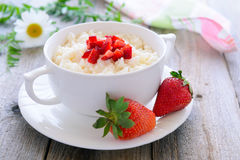Rice porridge with slices of strawberry - tasty breakfast Royalty Free Stock Images