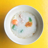 Rice porridge. And Soft-boiled egg pour with fried sliced garlic put in the white bowl on yellow background and take from top view Stock Image