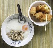 rice porridge topping pork and egg, eat with deep-fried doughstick royalty free stock photo