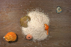 Rice poured on wood panel. The composition of sea shells added. Shells orange, gray, pink and green stock photography