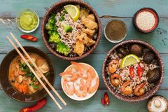 Rice with prawns, chicken, mushrooms, broccoli on a naked rustic background. Asian dishes. Concept of Asian food. Flat lay. royalty free stock images