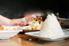 Rice is prepared for a meal. Selective focus at rice on white plate prepared for some meal on the meal table, there is people sitting for a meal royalty free stock photo
