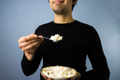 Rice pudding?. Young multiracial man with a bowl of rice pudding Stock Images