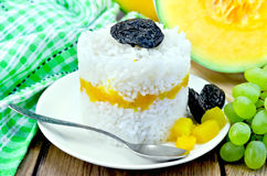 Rice with pumpkin and grapes on the board Royalty Free Stock Image