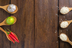 Rice, Red chilli, garlic and lemon on wooden background Stock Photography