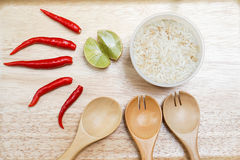 Rice, red chilli, lime on the wooden tray with spoon. Food ingredients consisted of rice, red chilli, lime on the wooden tray with spoon Royalty Free Stock Images