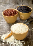 Rice - red, white and wild in a bowls with  chopsticks on wooden Royalty Free Stock Images