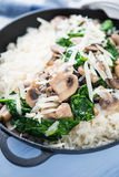 Rice risotto with mushrooms, parmesan and spinach close up on blue wooden background. Italian cuisine Stock Photo