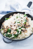 Rice risotto with mushrooms, parmesan and spinach close up. Italian cuisine Royalty Free Stock Photography