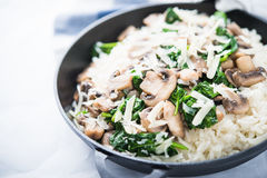 Rice risotto with mushrooms, parmesan and spinach close up. Italian cuisine Stock Photo
