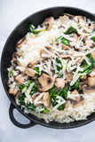 Rice risotto with mushrooms, parmesan and spinach top view on white background. Italian cuisine Stock Photo
