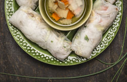 Rice rolls with transparent noodles inside  on a green plate with hearbs and vegetable soup  on dark wooden rustic background clos Stock Photography