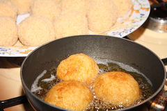 Rice's arancini. Fried arancini of rice in hot oil Royalty Free Stock Photo