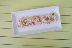 Rice salad in a white tray on green wood from above stock image