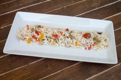 Rice salad in a white tray on wood royalty free stock photo