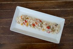 Rice salad in a white tray on wood from above stock images