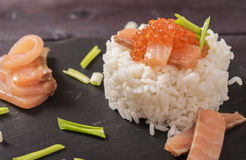 Rice, salmon, red caviar and chives. On a black shale plate Royalty Free Stock Photo