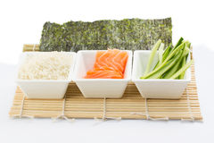 Rice salmon and sliced cucumber in white dish with nori on bamboo mat Stock Photography
