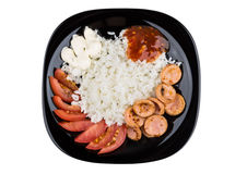 Rice and sausage with tomatoes, ketchup, mayonnaise in black pla Royalty Free Stock Photo