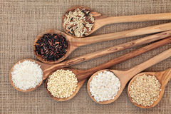 Rice Selection. Rice varieties in olive wood spoons over hessian background Royalty Free Stock Images