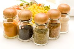 Rice, shrimps and spices. Rice and shrimps onthe plate behind some bottles with spices Stock Photography