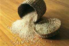 Rice in Small Basket. Rice in a small basket on a wooden table Stock Photography