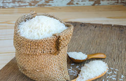 Rice in small hemp sacks and in wooden spool on wooden Royalty Free Stock Photo