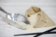 Rice in small hessian bag on wooden table royalty free stock photos