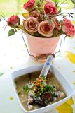 Rice soup with beautiful flower on the table. Rice soup with beautiful pink flower on the table Royalty Free Stock Image