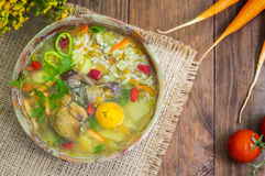 Rice soup with chicken navels and egg yolk. Wooden rustic background. Top view. Close-up Stock Image