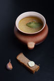 Rice soup in a clay pot on a black table or background Stock Photos