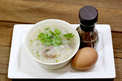 Rice Soup with pork. And machines in a white Cup. With eggs and cooked as a visual component Stock Photos