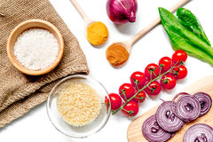Rice, spices and vegetables for paella on white desk background top view Stock Photos