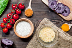 Rice, spices and vegetables for paella on wooden desk background top view Royalty Free Stock Photography